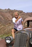 Laughing Retiree Riding Antique Car in the Desert Royalty Free Stock Photography