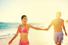 Laughing romantic couple summer vacation beach fun. Laughing happy romantic couple summer vacation beach fun. Joyful multi-ethnic young couple laughing elated Stock Images