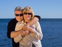 Laughing romantic mature couple enjoy a day at the sea. Laughing romantic mature couple enjoying a day at the sea standing in a loving embrace in their casual Stock Photos