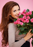 Laughing romantic woman with roses. Laughing romantic sexy woman with long brunette hair holding a large bouquet of pink roses for her anniversary or Valentines Stock Images