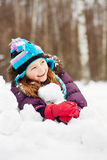 Laughing rosy girl lies on snowdrift royalty free stock photo
