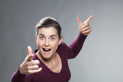 Laughing 30s woman glowing from within with hands up Stock Photo