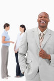Laughing salesman with colleagues behind him Stock Photography