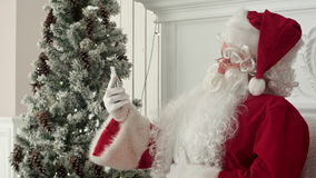Laughing Santa Claus reading Christmas messages from kids