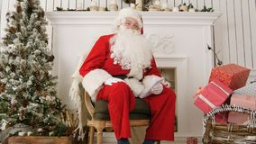 Laughing Santa sitting in a chair in his Christmas workshop. Professional shot on Lumix GH4 in 4K resolution. You can use it e.g. in your commercial video Royalty Free Stock Photography