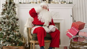 Laughing Santa sitting in a chair in his Christmas workshop stock video