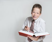 Laughing schoolboy reads a big red book Royalty Free Stock Photography