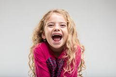 Laughing schoolgirl with curly hair. Portrait of laughing preteen girl with curly hair against plain background Royalty Free Stock Images