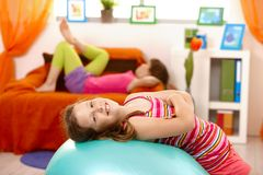 Laughing schoolgirl lying on gym ball Stock Image