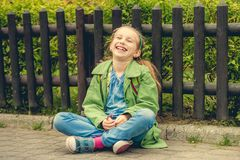 Laughing schoolgirl  sitting on the street Royalty Free Stock Photography
