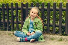 Laughing schoolgirl  sitting on the street Stock Photography