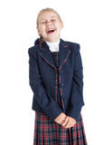 Laughing schoolgirl, standing in dark blue uniform isolated white background Royalty Free Stock Photos
