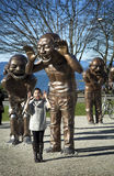 Laughing sculpture in Vancouver. VANCOUVER-CANADA, 8 february 2016: Tourist posing and imitate sculpture from Yue Minjun The bronze characters depict the artist' stock photos