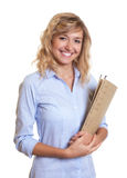Laughing secretary with curly blond hair and file Stock Photo