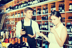 Laughing seller man giving sample taste of wine. Laughing seller men wearing apron giving sample taste of wine in glass to women customer in wine store Royalty Free Stock Photography