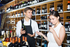 Laughing seller man giving sample taste of wine. Laughing seller men wearing apron giving sample taste of wine in glass to women customer in wine store Royalty Free Stock Image
