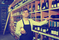 Laughing seller man promoting bottle of wine. Laughing seller man wearing apron promoting bottle of wine in wine store Stock Image