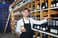 Laughing seller man promoting bottle of wine. Laughing seller man wearing apron promoting bottle of wine in wine store Stock Images