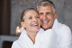 Laughing senior couple embracing at spa. Smiling husband embracing cheerful wife from behind at spa. Laughing mature couple enjoying a romantic hug at wellness royalty free stock photo