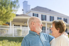 Laughing Senior Couple in Front Yard of House. Happy Senior Couple in the Front Yard of Their House Royalty Free Stock Image