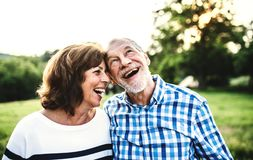 A laughing senior couple in love outdoors in nature. A joyful senior couple in love outdoors in nature, laughing royalty free stock images
