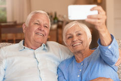 Laughing senior couple taking selfies with their cellphone at home Royalty Free Stock Images