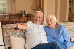 Laughing senior couple watching television at home. Laughing senior men pointing a remote while sitting with his wife on a sofa in their living room watching royalty free stock photography