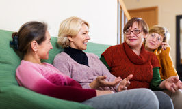 Laughing senior friends chatting. In living room royalty free stock photo