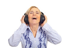 Laughing senior with headphones. Beauty senior woman listening in headphones and laughing isolated on white background stock photos