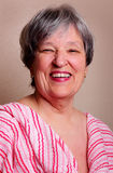 Laughing Senior Lady. A laughing pretty older lady with short grey hair. Shallow depth of field stock photos