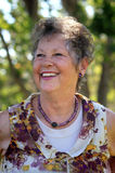 Laughing Senior Lady. A closeup of a laughing senior citizen with curly hair. Shallow depth of field stock photos