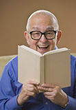 Laughing senior male reading a book. On a couch. Vertical royalty free stock photo