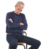 Laughing senior man sitting with arms crossed. Happy senior man laughs with arms crossed while sitting on stool and leaning back. He wears dark blue jeans and v stock image