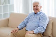 Laughing senior. Senior man sitting at home and laughing stock photos