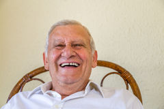 Laughing senior man. In white shirt with gray hair over yellow wall, toothy smile while sitting stock images