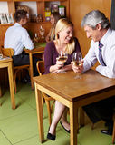 Laughing senior people drinking. Two happy laughing senior people drinking white wine in restaurant royalty free stock image