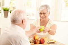 Laughing senior wife getting apple from husband. Laughing senior wife getting green apple from husband, sitting at kitchen table, having breakfast Royalty Free Stock Images
