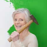 Laughing senior woman doing interior decorating. Laughing senior woman with a vivacious smile doing interior decorating at home standing with a hammer in front stock photos