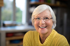 Laughing senior woman in the kitchen. Portrait of laughing senior woman in the kitchen stock photography