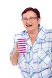 Laughing senior woman with mug. Happy laughing senior woman holding mug, isolated on white background royalty free stock photos