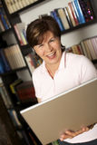 Laughing senior woman standing with laptop. Laughing modern senior woman standing in front of bookshelf and holding a laptop royalty free stock photos