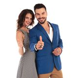 Laughing sexy couple giving thumbs up sign. While standing on white background Stock Image