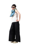 Laughing short hair girl wearing sunglasses with hands on hips pose Royalty Free Stock Photos