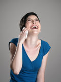 Laughing short hair woman while talking on the mobile phone Royalty Free Stock Photos