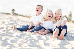 Laughing Sibling Children Sitting at the Beach Stock Images
