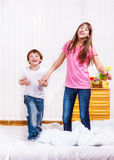 Laughing siblings jumping Stock Images