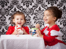 Laughing sisters. Portrait of sisters sitting at a table drinking from Christmas mugs Royalty Free Stock Photo