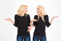 Laughing sisters twins looking at each other and shrugging shoulders Royalty Free Stock Photography