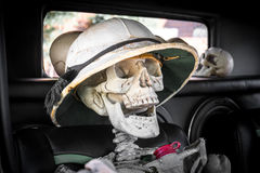 Laughing Skeleton with Safari Hat in a Car. Laughing skeleton with a Safari hat in the passenger seat of an old car, ready for a ride on the Day of the Dead or stock photos