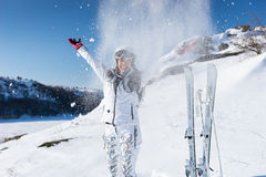 Laughing skier throwing snow on herself Stock Images